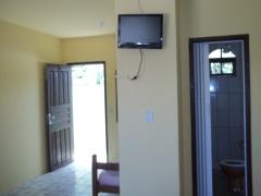 Quarto casal, com tv, ventilador de teto e banheiro privativo.
