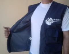 Colete de brim forrado, com vários bolsos e zíper, para uso profissional.