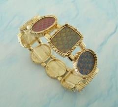 Bracelete dourado com tecido holográfico que muda de cor conforme o angulo de visão.
