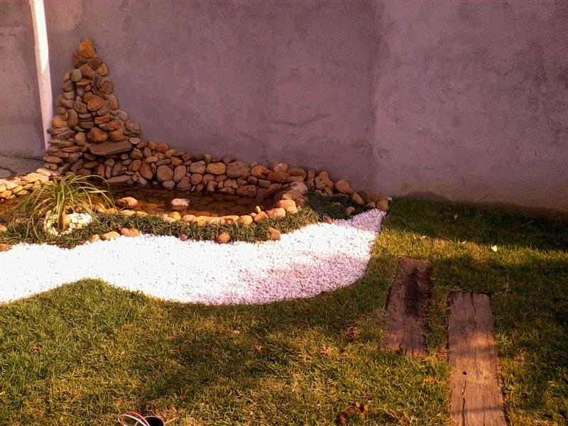 Fonte, seixos de rio, pedrisco branco, dormentes e grama esmeralda.