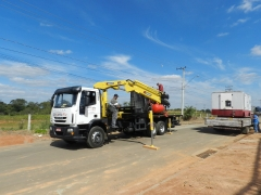 Caminhão munck descarregando equipamento