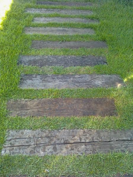 Temos aqui um caminho com dormentes e grama esmeralda, criação e implantação de Arte Paisagismo & Jardinagem.