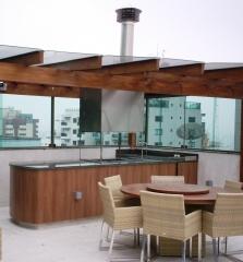 Churrasqueira com coifa quadrada, cobertura em pergolado e com fechamento em vidro. executado pela bella telha e projetado por marcela franchini